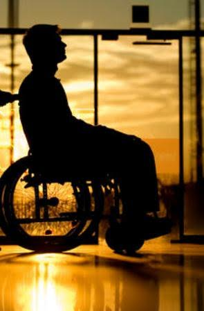 Silhouette of a woman pushing a male patient sitting in a wheelchair